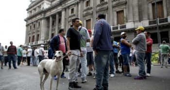 A supporter of greyhound racing stands with his dog outside Congress in Buenos Aires, Argentina, Wednesday, Nov. 16, 2016. Lawmakers are expected to vote Wednesday on a law that would prohibit greyhound racing in the country. (AP Photo/Victor R. Caivano)
